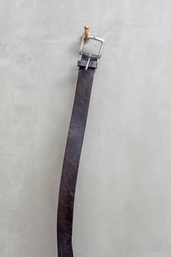 black-leather-belt-hanging-hanger-exposed-concre-concrete-wall-bathroom-44981737